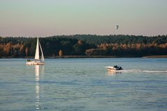 Beautiful lake landscape, yacht, balloon, birds and sunset. Blue waves, boat and horizon line on water royalty free stock images