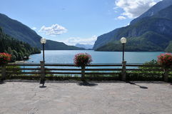 Beautiful Lake, Molveno, Italy. Images shows Molveno Lake at the foot of the Brenta Dolomites. In the front a stone terrace in the front, a wooden fence and two Royalty Free Stock Photo