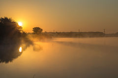 Beautiful lake in the morning mist and rising sun Royalty Free Stock Images