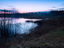 Beautiful lake near city with colorful sunset sky. Tranquil vibrant landscape Royalty Free Stock Photo
