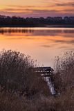 Beautiful lake near city with colorful sunset sky. Tranquil vibrant landscape Stock Photography