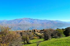 Beautiful lake scape. A beautiful lake scape with reflected mountains and the basilica church of Saint Achilles in the small Prespa lake in Greece early in royalty free stock images