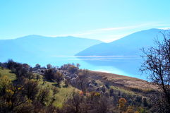 Beautiful lake scape. A beautiful lake scape with reflected mountains and many trees in the small Prespa lake in Greece early in winter royalty free stock photography