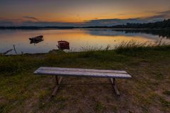 Beautiful lake sunset with bench on shore and fisherman boat Stock Photography