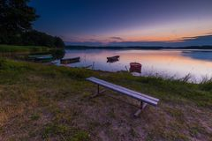 Beautiful lake sunset with bench on shore and fisherman boat Royalty Free Stock Photos