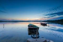 Beautiful lake sunset with fisherman boats Royalty Free Stock Photos