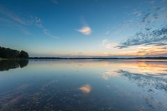 Beautiful lake at sunset landscape with cloudy sky reflecting in water Stock Image