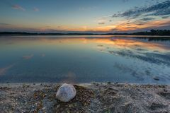 Beautiful lake at sunset landscape with cloudy sky reflecting in water Royalty Free Stock Photo