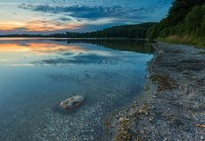 Beautiful lake at sunset landscape with cloudy sky reflecting in water Stock Images