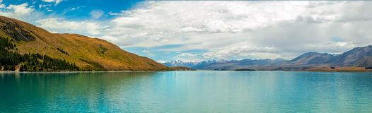 Beautiful Lake Tekapo Panorama, New Zealand. The turquoise waters of Lake Tekapo fringed by the Southern Alps in Canterbury, New Zealand on a fair summer day Royalty Free Stock Images
