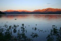 Beautiful lake Tekapo at sunset. Beautiful lake Tekapo at dusk with mountains peaks in sunset colors. Lake Tekapo. South Island. New Zealand Stock Photo