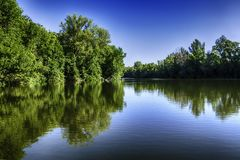Beautiful landcsape, trees reflection in the lake water under blu. E sky Stock Images
