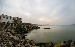 Beautiful landscape of abandoned house on rocky seashore at sunset time. Cloudy weather. Caspian Sea, Azerbaijan. Novkhani stock photography