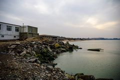 Beautiful landscape of abandoned house on rocky seashore at sunset time. Cloudy weather. Caspian Sea, Azerbaijan. Novkhani royalty free stock photo