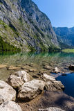 Beautiful landscape of alpine lake with crystal clear green water and mountains in background, Obersee, Germany.  Royalty Free Stock Images