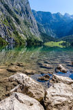 Beautiful landscape of alpine lake with crystal clear green water and mountains in background, Obersee, Germany.  Stock Image