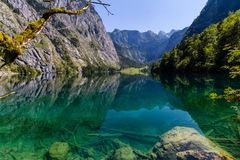 Beautiful landscape of alpine lake with crystal clear green water and mountains in background, Obersee, Germany.  Stock Photography