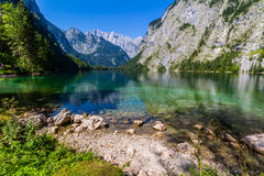 Beautiful landscape of alpine lake with crystal clear green water and mountains in background, Obersee, Germany.  Royalty Free Stock Image