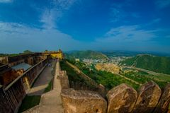 Beautiful landscape of Amber Fort with some people walking around, with green trees, mountains and small houses near Royalty Free Stock Photos