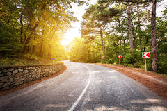 Beautiful landscape with asphalt road,green forest and road sign at colorful sunrise in summer. Crimean mountains. Stock Photo