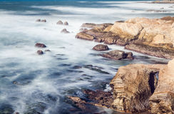 Beautiful landscape in the beach with stones on a long exposure and motion wave Royalty Free Stock Images