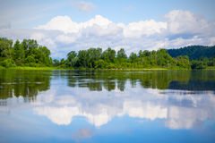 Beautiful landscape with blue sky and white clouds reflected in Royalty Free Stock Photo