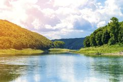 Beautiful landscape with blue water in a river and green trees i. N forest on mountain hills Stock Photography