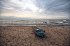 Beautiful landscape of Boat on the beach in cloudy weather. Vintage Boat in the seashore. Azerbaijan Caspian Sea Novkhani Royalty Free Stock Photo