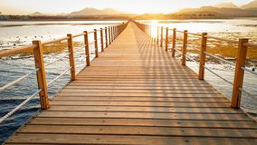 Beautiful landscape of calm ocean waves and long wooden pier. Amazing jetty at sea aagainst sunset over the mountains stock image