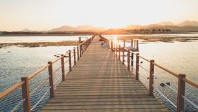 Beautiful landscape of calm ocean waves and long wooden pier. Amazing jetty at sea aagainst sunset over the mountains stock photo
