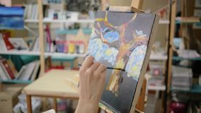 Beautiful landscape on canvas in art workshop, detail view, hand of artist. Canvas with abstract nature image on easel in art studio, close-up view. Hand of stock video
