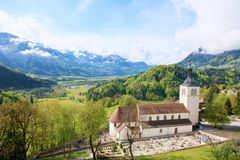 Beautiful landscape with church in Gruyeres,Switzerland. Alps mountains and fields, pretty summer day. stock photos