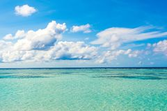 Beautiful landscape of clear turquoise Indian ocean. Water villas and a tropical island on the horizon, Maldives islands Royalty Free Stock Photography