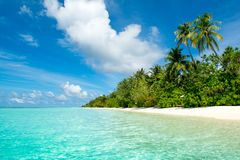 Beautiful landscape of clear turquoise Indian ocean. Water villas and a tropical island on the horizon, Maldives islands Stock Image