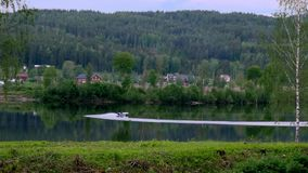 Beautiful landscape clip of forested hills and a lake with a speed motor boat making a 180 degree turn on a cloudy day. Beautiful landscape clip of forested stock video footage