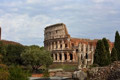 Beautiful landscape of Coliseum near the green trees under the b. Lue summer sky. Rome Stock Photography