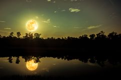 Beautiful landscape of colorful sky and clouds. Full moon with reflection above silhouette of trees and river. Serenity nature in. Gloaming time. Outdoors at stock photo