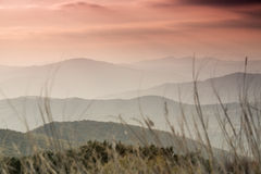 Beautiful landscape and colorful sunset over hills. Stock Photos