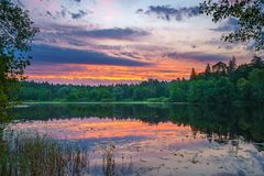 Beautiful sunrise on a lake. Beautiful landscape with corful sunrise over the forest lake Royalty Free Stock Photos