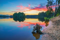 Bright sunset on a lake. Beautiful landscape with corful sunset over the forest lake Stock Photo