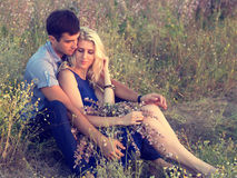 Beautiful landscape and couple in love with flowers on sunset Royalty Free Stock Photos