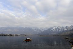 A beautiful landscape at the Dal Lake Kashmir, India during winter. Local people using boat at the lake Stock Photos