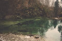 Emerald pool among hill reflect green tree and forest stock photography
