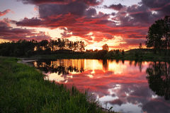 Beautiful landscape with fiery sunset over the lake Royalty Free Stock Images