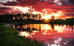 Beautiful landscape with fiery sunset over the lake Stock Photo