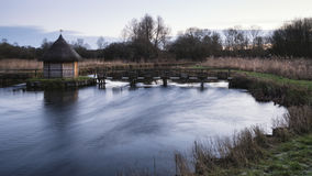 Beautiful landscape on frosty Winter morning of eel traps over f Stock Image