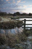 Beautiful landscape on frosty Winter morning of eel traps over f Royalty Free Stock Image