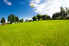 Beautiful landscape of golf course with flagstick. Beautiful scenery of green golf course with flagstick in the distance at sunny day Stock Photos