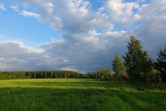 Beautiful landscape. Green field and cloudy sky. Central Russia. Moscow region.  royalty free stock photos