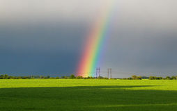 Beautiful landscape with green meadow and a bright rainbow in th Royalty Free Stock Photo